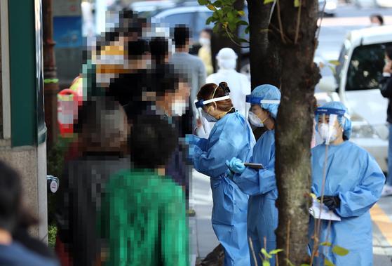 9일 오전 대전시 서구 만년동 서구보건소 선별진료소에서 신종 코로나바이러스 감염증(코로나19) 검사를 받기 위해 시민들이 줄을 서고 있다. 전날 대전에서는 중학생을 포함한 일가족 7명이 코로나19 확진 판정을 받았다. 연합뉴스