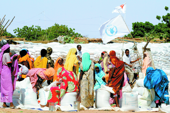 노르웨이 노벨위원회는 9일(현지시간) 유엔 세계식량계획(WFP)이 올해 노벨 평화상 수상자로 선정됐다고 발표했다. 사진은 2014년 아프리카 수단의 난민 여성들이 다르푸르 인근의 실향민을 위한 킬마 캠프에서 WFP가 제공하는 구호 식량을 받는 모습. [AFP=연합뉴스]