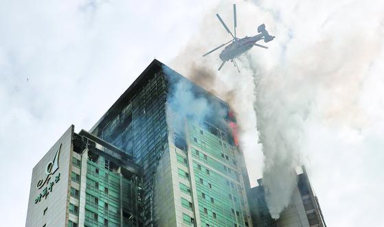 9일 낮 울산시 남구 주상복합건물 삼환아르누보에서 화재가 완전히 진화되지 않아 소방대원들이 진화작업을 펼치고 있다. 송봉근 기자