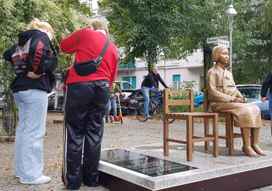 지난달 25일(현지시간) 독일 수도 베를린에 설치된 '평화의 소녀상'에 쓰인 비문을 지나가던 시민들이 읽고 있다. [연합뉴스]