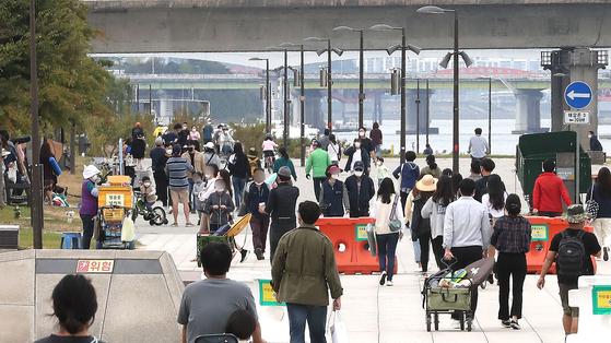 정부가 두 달 간 지속했던 서회적 거리두기 2단계를 1단계로 완화하기로 했다. 11일 오전 서울 영등포구 여의도 한강공원에서 시민들이 나들이를 즐기고 있다. 뉴스1