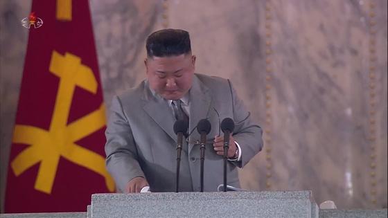 김정은 북한 국무위원장이 10일 노동당 창건 75주년 열병식 연설 도중 재난을 이겨내자고 말하며 울컥한 듯 안경을 벗고 눈물을 훔치고 있다. [연합뉴스]