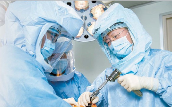 강북연세병원 박영식 병원장(오른쪽)이 수술실 내부 압력을 높여 밖의 공기가 안으로 들어오지 못하게 하는 무균 양압수술실에서 전신을 감싼 우주복 같은 수술복을 입고 무릎 인공관절 수술을 하고 있다. 김동하 객원기자