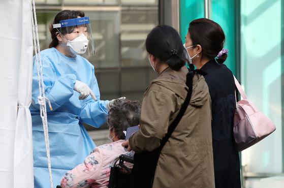 9일 오전 서울 중구 국립중앙의료원에 마련된 선별진료소에서 시민들이 신종 코로나바이러스 감염증(코로나19) 진단 검사를 받기 전 의료진의 안내를 받고 있다. 뉴스1