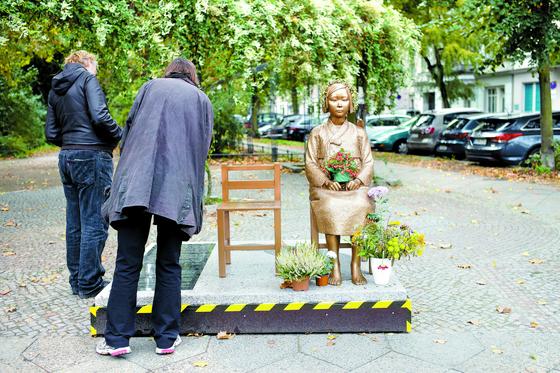 9일(현지시간) 독일 베를린에 있는 '평화의 소녀상' 앞에 멈춰 서 비문을 읽고 있는 시민들. 일본군 위안부 피해자를 기리기 위한 조형물이지만 시 당국이 철거를 명령했다. [AP=연합뉴스]