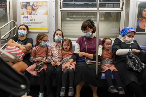 마스크를 착용하고 미국 뉴욕 지하철을 탄 가족들의 모습. AP=연합뉴스