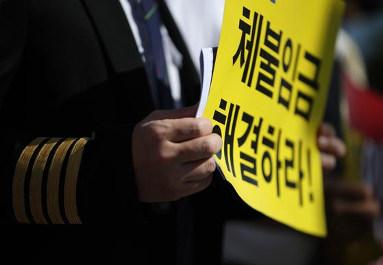 지난달 22일 오전 서울 여의도 국회 앞에서 열린 '이스타항공 노동자 고용유지 촉구를 위한 조종사 노동조합 합동 기자회견'에서 참가자들이 손팻말을 들고 있다. 연합뉴스