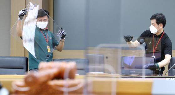 지난 8월 세종시 정부세종청사 국무회의장에 관계자들이 코로나19 감염 예방을 위한 비말 차단 투명 칸막이를 설치하고 있다. 투명 칸막이와 공간 전체 환기보다는 개인별로 착용할 수 있는 환기시스템이 더 효과적이란 주장이 나오고 있다. 연합뉴스