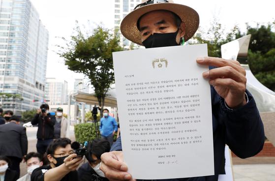 북한 피격으로 사망한 공무원 A씨 형 이래진 씨가 14일 오후 인천시 연수구 해양경찰청 앞에서 기자회견을 갖고 문재인 대통령이 북한 군에 의해 사망한 해양수산부 공무원 이모(47)씨의 고교생 아들에게 보낸 답장을 보여주고 있다. 뉴시스