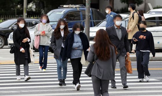 쌀쌀한 날씨를 보이는 지난 13일 오전 서울 송파구 잠실역 사거리에서 출근길 시민들이 발걸음을 옮기고 있다. 연합뉴스