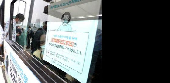 버스에서 마스크 착용 요구를 받자 난동을 부린 남성이 경찰에 체포됐다. 사진은 버스에 부착된 마스크 착용에 대한 안내문. 연합뉴스
