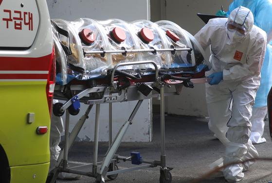 지난 14일 무더기 코로나19 확진자가 발생한 부산 만덕동 해뜨락요양병원에서 119 구급대원이 부산의료원 등에 환자를 이송하고 있다. 송봉근 기자