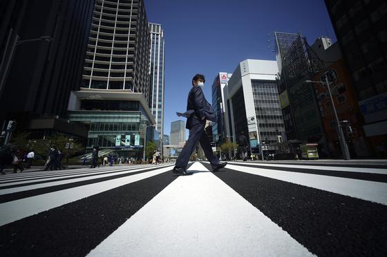 도쿄에서 마스크를 쓴 시민이 텅 빈 도로를 건너고 있다. [AP=연합뉴스]