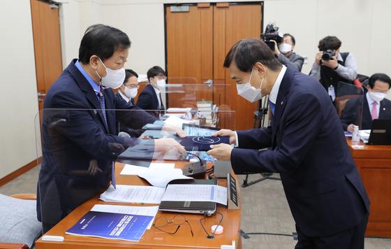 이주열 한국은행 총재(오른쪽)가 16일 한국은행에 대한 국회 국정감사에서 윤후덕 상임위원장에게 증인 선서문을 제출하고 있다. 민주당 의원들은 이날 국정감사에서이 총재의 '재정준칙' 발언을 강하게 비판했다. [뉴스1]
