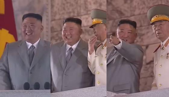10일 열병식에서 김정은 국무위원장이 열병 부대 행진을 보며 웃음을 보였고 옆에 있던 이병철 당중앙 군사위 부위원장과 대화하고 있다. [조선중앙TV 화면 캡처]