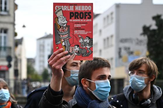 17일 프랑스에서 한 남성이 참수된 중학교 역사 교사를 추모하며 샤를리 에브도 매거진을 들고 행진하고 있다. [AFP=연합뉴스]