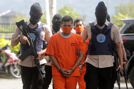 지난 13일 인도네시아 경찰들이 마약사범을 체포해 연행하고 있다. [연합뉴스]