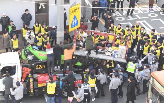 지난해 12월 10일 경남 창원시 마산합포구 서성동 성매매 집결지 입구에서 창원시 관계자가 폐쇄회로(CC)TV를 설치하려고 하자 업주와 종업원이 이를 저지하고 있다. 연합뉴스