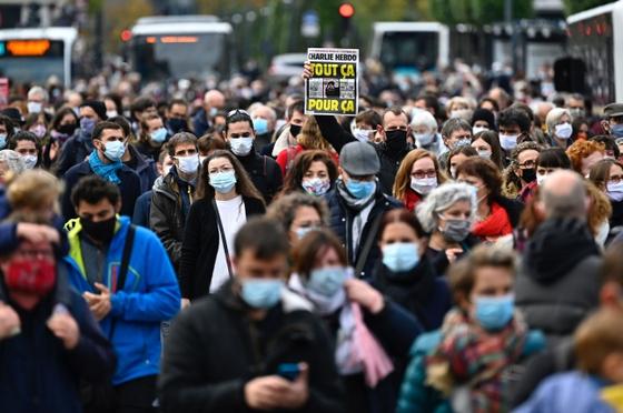 참수당한 프랑스 중학교 교사를 추모하는 시위에서 한 참가자가 '이 모든 것, 단지 그것 때문에'라는 글로 커버를 장식한 주간지 샤를리 에브도를 들어 보이고 있다. [AFP=연합뉴스]