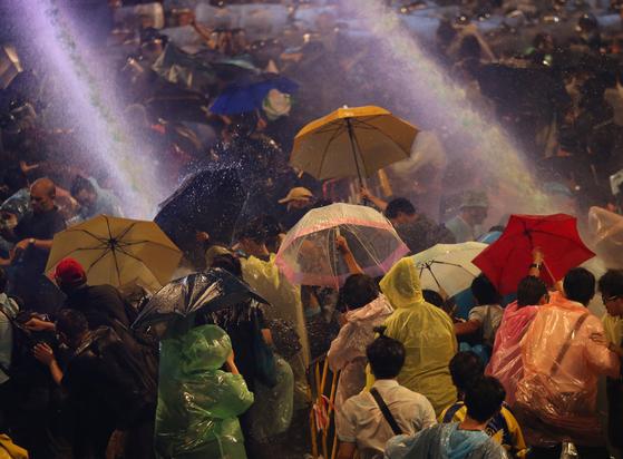지난 16 일 태국의 민주화 시위대를 향해 경찰이 물대포를 쏘고있다. 시위대는 우산을 넓혀 물을 피하고있다. [EPA=연합뉴스]