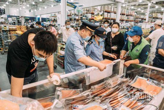 지난 6월 베이징 신파디 농수산물시장에서 코로나 환자가 발생하자 중국 경찰이 슈퍼와 상점을 돌며 육류와 해산물 제품을 검사하고 있다. 당시엔 수입 연어가 의심을 받았다. [중국 환구망 캡처]