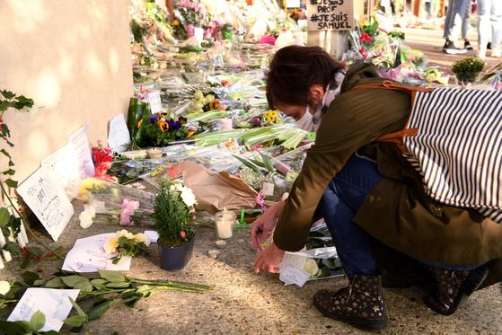 16일(현지시간) 오후 5시께 파리에서 북서쪽으로 30km 떨어진 이블린주 콩플랑생토노린 학교 인근 거리에서 중학교 역사 교사인 사뮤엘 프티(47)가 참수된 채 발견됐다. 한 여성이 교사를 추모하고 있다. AFP=연합뉴스