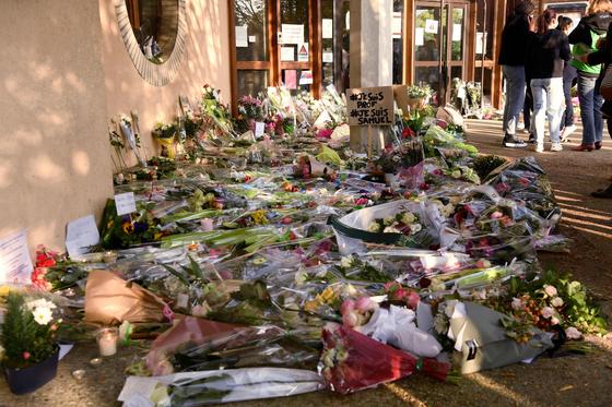 17일(현지시간) 프랑스 이블린주 콩플랑 생토노린 학교 인근에서 참수된 채 발견된 중학교 역사 교사를 추모하는 플래카드와 꽃이 놓여 있다. [AFP=연합뉴스]