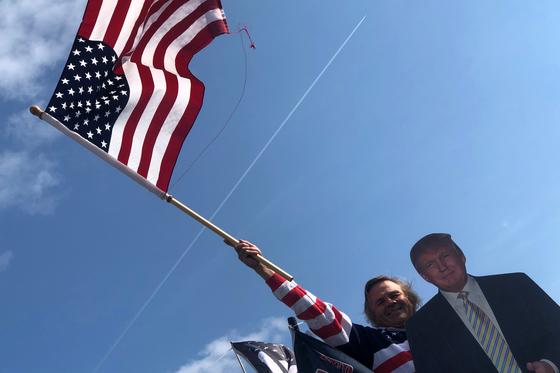 도널드 트럼프 미국 대통령 지지자가 18일 미국 뉴욕에서 트럼프 대통령 등신대 뒤에서 성조기를 흔들고 있다. [로이터=연합뉴스]
