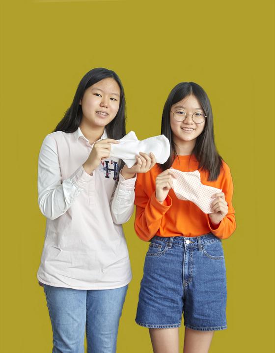 김수안(왼쪽)·백채희 학생기자가 세계교육문화원의 참여 기부 캠페인 중 대안 생리대 만들기에 도전했다. 직접 만든 대안 생리대를 들어 보인 두 학생기자.