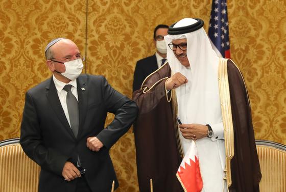 18일 바레인 마나마에서 수교 합의를 한 벤 샤밧 이스라엘 국가안보보좌관(왼쪽)과 알자야니 바레인 외무장관이 서로의 팔꿈치를 치고 있다. [EPA=연합뉴스]