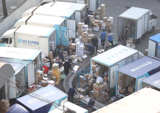 택배 노동자들의 과로사가 잇따르는 가운데 20일 서울의 한 택배 물류센터에서 작업자들이 산더미처럼 쌓인 택배 박스를 옮기고 있다.[뉴스1]