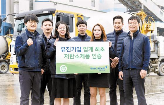 저탄소 레미콘 개발에 힘써 온 유진기업의 직원들이 '업계 최초 저탄소제품 인증' 기념 팻말을 들고 축하하고 있다.