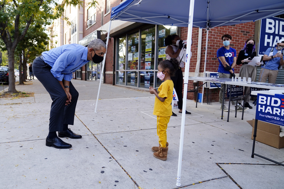 버락 오바마 전 대통령이 21일(현지시간) 펜실베이니아주에서 민주당 대선 후보 조 바이든 지지 유세에 나섰다. 선거 사무소 근처에서 만난 아이와 눈을 맞추고 있다. [AP=연합뉴스]