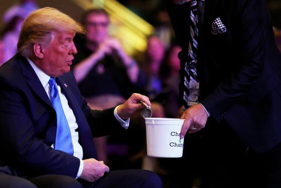 18일 네바다주 라스베이거스의 한 교회 예배에 참석한 트럼프 대통령이 돈을 센 뒤 헌금하고 있다. 로이터=연합