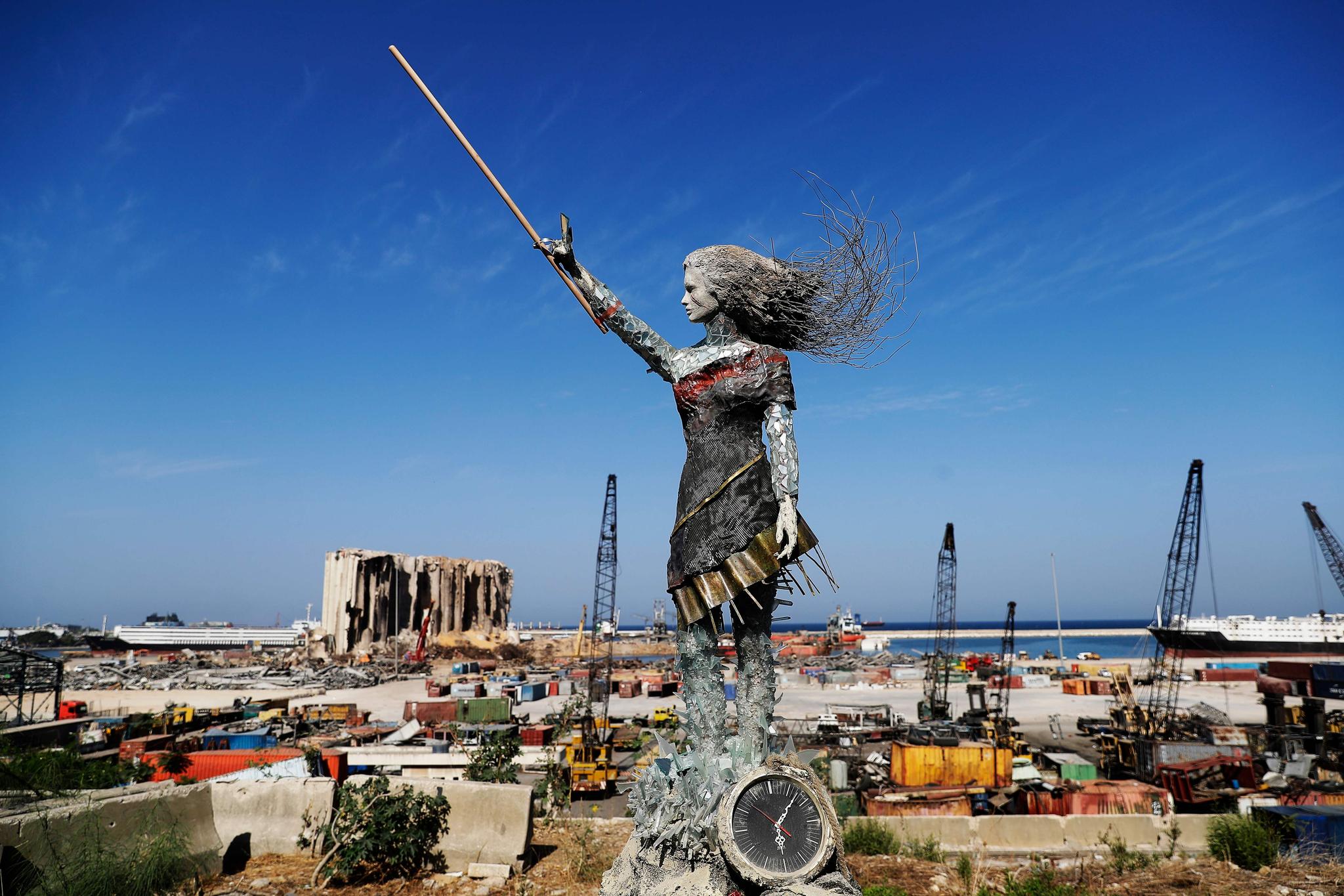 20일(현지시간) 복구 작업이 한창인 레바논 베이루트 항구에 여성 동상이 세워져 있다. 레바논 예술가들은 폭발이 있었던 지난 8월 4일 오후 6시 7분에 멈춘 시계와 폭발 현장의 파편 등으로 이 동상을 만들었다. AFP=연합뉴스