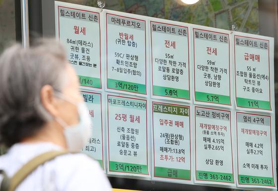 서울 마포구의 한 부동산중개소 앞을 시민이 지나고 있다. 연합뉴스.