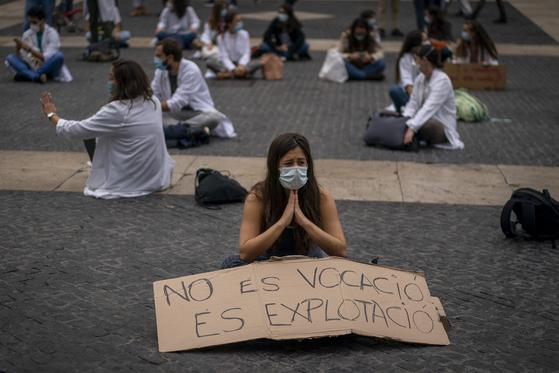 """22일(현지시간) 스페인 바르셀로나에서 의과대 레지던트들이 시위를 벌이고 있다. 팻말에는 """"이건 착취지 (의료인의) 소명이 아니다""""라고 적혀 있다.[AP=연합뉴스]"""