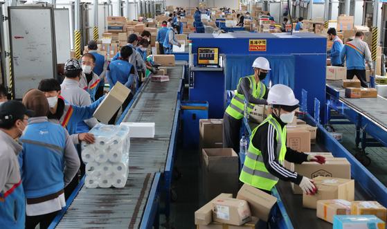 지난 21일 오전 서울 서초구에 있는 CJ대한통운 강남2지사 터미널의 작업장에서 택배기사들이 배달할 물건을 분류하는 작업을 하고 있다. [뉴스1]