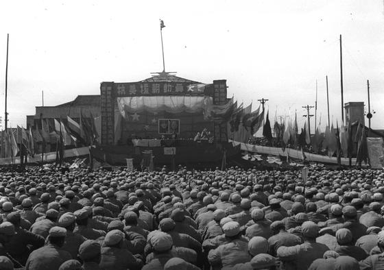 1951년 중국인민지원군 모 부대에서 열린 항미원조 동원 대회. 무대에 오성홍기와 펑더화이와 마오쩌둥의 초상화가 걸려 있다. [이미지차이나]