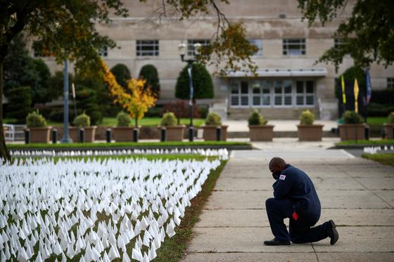 23일(현지시간) 코로나19 희생자를 추모하기 위해 미국 워싱턴에 설치된 수전 브레넌 퍼스텐버그의 작품 '어떻게 미국에 이런 일이' 앞에서 한 남성이 무릎을 꿇고 묵념하고 있다. [로이터=연합뉴스]