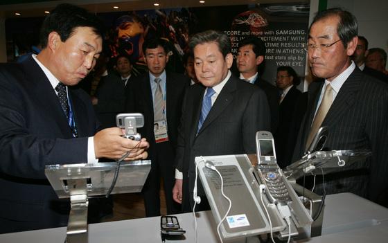 이건희 삼성그룹 회장이 아테네 삼성홍보관을 방문해 전시된 휴대폰을 둘러보고있다. 오른쪽은 윤종용 삼성전자 부회장. [아테네=올림픽사진공동취재단]