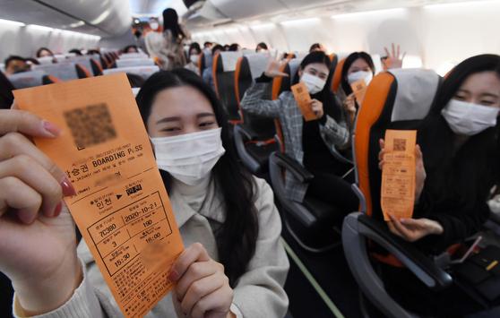 지난 23일 제주항공 기내에서 승객들이 탑승권을 들어 보이고 있다. [사진 공항사진기자단]