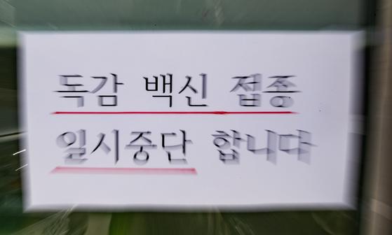 지난 23일 서울의 한 병원에 독감 예방접종 일시 중단 안내문이 게시돼 있다. 뉴스1