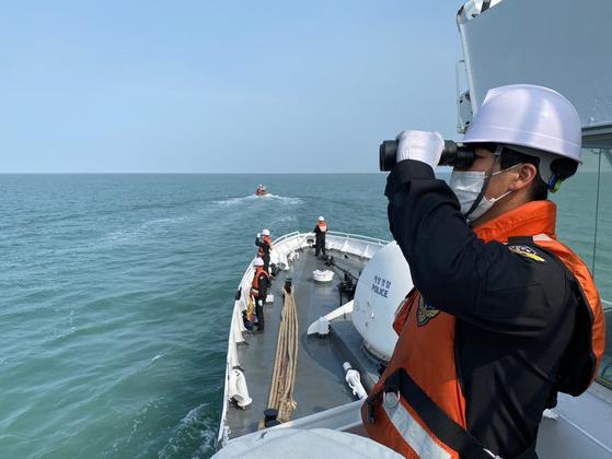 """지난 3일 해경이 경비함에서 북한에 의해 사살된 해양수산부 공무원 이모(47)씨의 시신 및 유류품을 수색하는 모습. 이날 농림축산식품해양수산위원회 국정감사에선 """"해경이 잘못된 중간수사결과를 발표해 이씨 유족들이 큰 상처를 입었다""""는 야당의 비판이 쏟아졌다. [해양경찰청 제공]"""