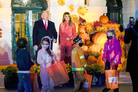 도널드 트럼프 미 대통령 부부가 25일(현지시간) 백악관에서 열린 할로윈 행사에 사탕을 받으러 온 어린이들을 맞이하고 있다. [AP=연합뉴스]