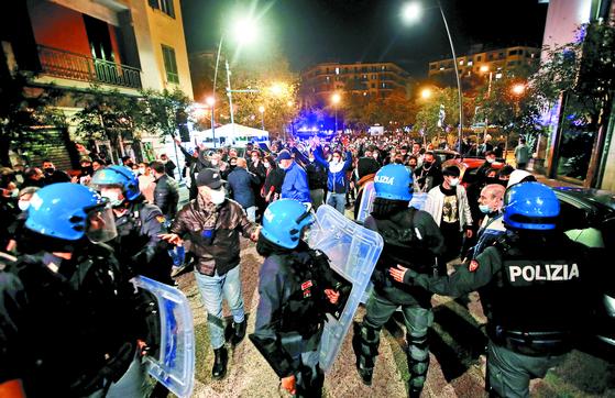 프랑스·이탈리아·스페인 등은 하루 수만 명의 코로나19 확진자가 발생하자 감염병 확산을 막기 위해 주요 지역에 야간 통행금지 조치를 내렸다. 25일(현지시간) 이탈리아 나폴리에서 식당·술집 등의 주인들이 야간 영업금지 조치에 항의하는 시위를 하자 경찰이 출동했다. [로이터=연합뉴스]