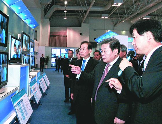 고(故) 이건희 삼성 회장(오른쪽 둘째)이 생전인 2004년 선진 제품 비교전시회에서 디지털TV에 대한 설명을 듣고 있다. 왼쪽은 이학수 당시 부회장, 오른쪽은 최지성 당시 사장. [사진 삼성전자]