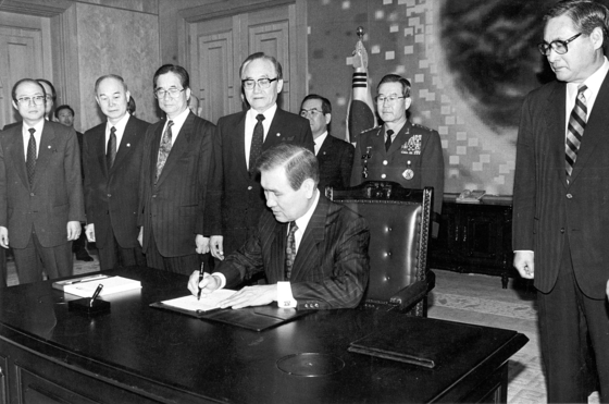 노태우 대통령이 1992년 2월 17일 정원식 총리(사진 맨 오른쪽) 등이 지켜보는 가운데 남북 기본합의서와 한반도 비핵화에 관한 공동선언에 서명하고 있다. [중앙포토]