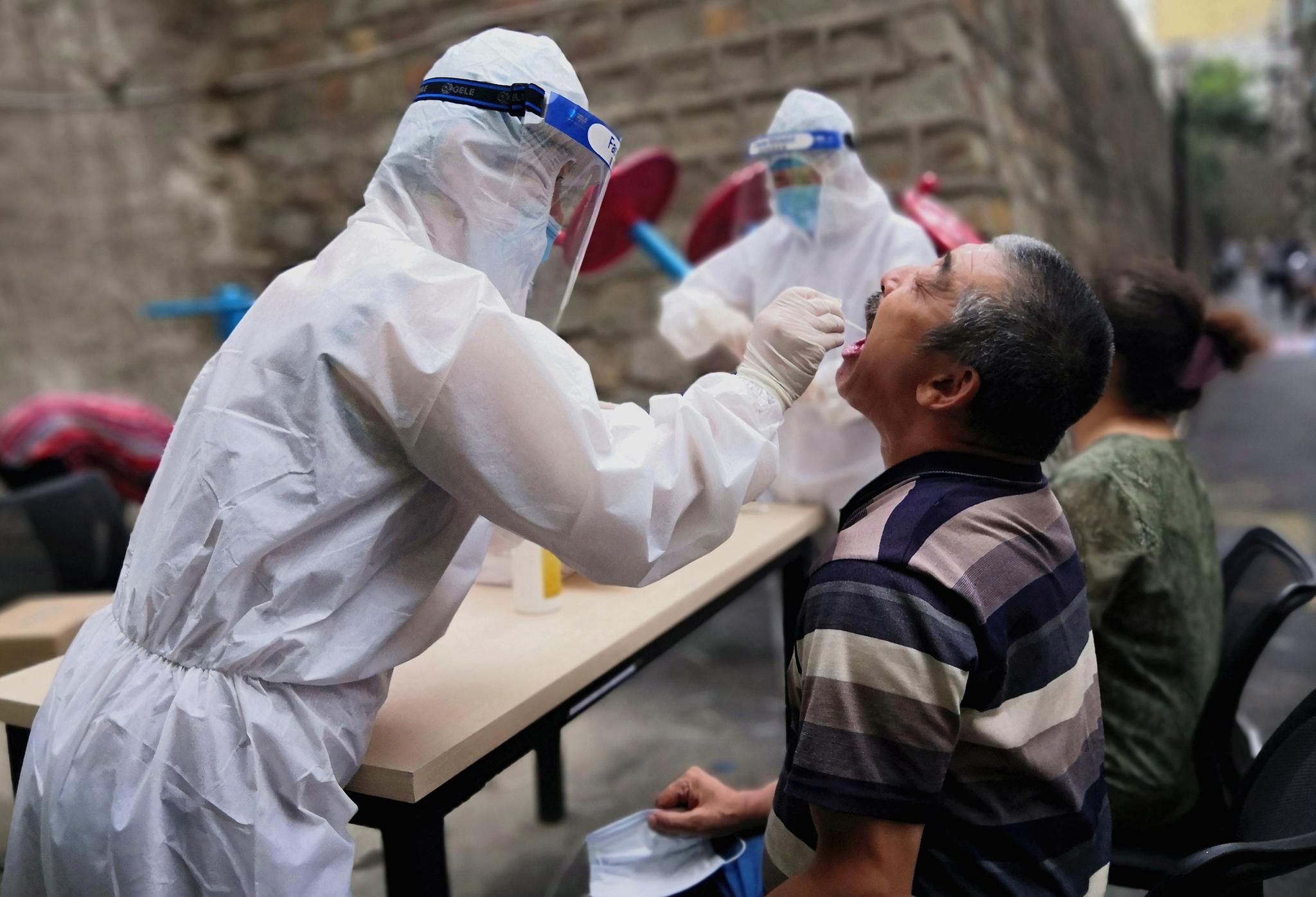사진은 지난 7월 코로나19가 확산한 신장위구르자치구의 우루무치시에서 방호복을 입은 의료진이 주민을 대상으로 핵산검사를 하고 있는 모습. 로이터=연합뉴스