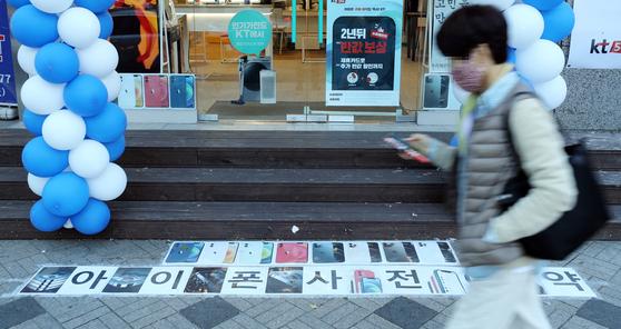 아이폰12 예약이 시작된 23일 서울 종로구 휴대전화 판매점 앞을 시민들이 지나고 있다. 연합뉴스